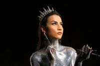 makeup artist with glitter bodyart and silver crown