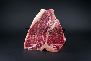 Raw dry aged wagyu porterhouse beef block offered as close-up on black background with copy space