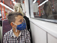 young boy with protective mask travels by subway