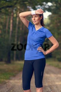 Sportliche Frau wischt sich Schweiß vom Gesicht