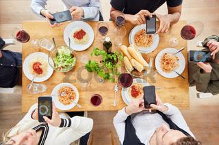 Freunde machen Foodie Foto mit Smartphone von Mahlzeit von oben