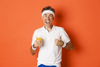 Concept of workout, gym and lifestyle. Image of active and healthy middle-aged sport guy, showing thumbs-up and drinking juice, smiling happy, standing over orange background