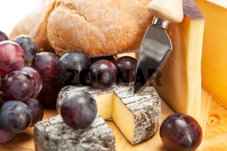 Cheese plate with red wine grapes and white bread