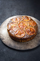 Traditional American upside-down bloody orange cake offered as closeup on a modern design tray with copy space