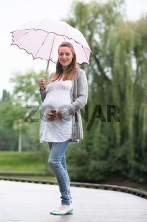 Pregant woman outside with umbrella