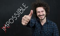 Portrait of man with Impossible text write on black board