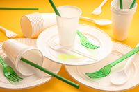 Disposable plastic dishware waste. Group of empty plates, cups, forks and utensils on yellow table