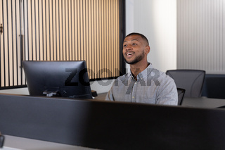 Smiling mixed race man sitting using computer in office