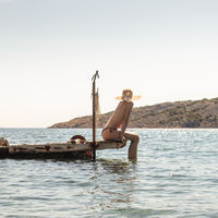 View of unrecognizable woman wearing big summer sun hat tanning topless and relaxing on old wooden pier in remote calm cove of Adriatic sea, Croatia