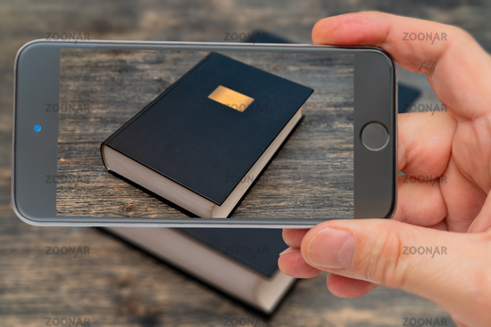 Book on smartphone screen. Big fat book. Knowledge is written in books. Training, education and storage of information.