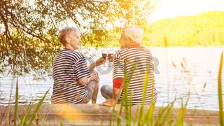 Älteres Paar Senioren beim Rotwein trinken am See