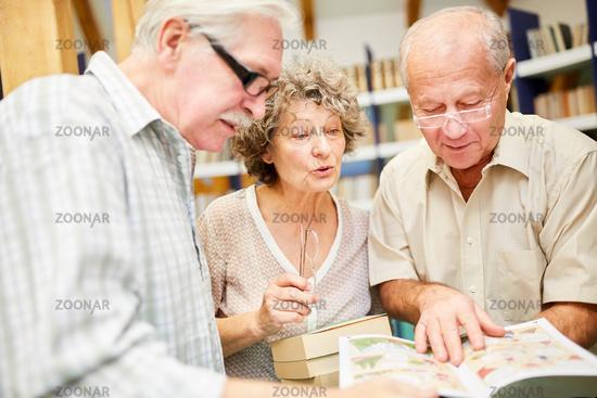 Gruppe Senioren mit Buch in Bücherei