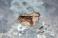 Background with old brown cracked stucco on a gray wall texture