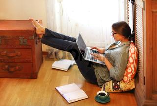 Woman designer using laptop on floor