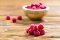 Fresh respberries lying on wooden table with full bowl in background.