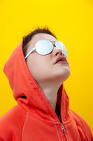Close up fashion portrait young beautiful woman in hoodie and white glasses. Alternative funky girl on a bright yellow background. Unusual youth fashion concept. Hot image.