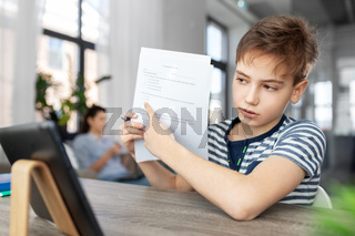 student boy with tablet computer learning at home