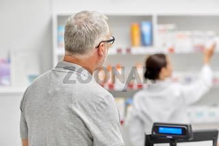 senior man buying medicine at pharmacy