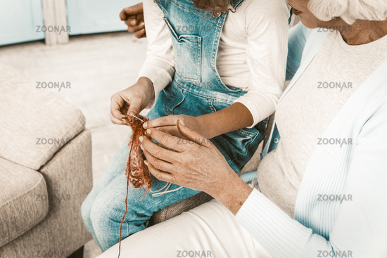 Granddaughter showing her grandmother what she has learn knitting.