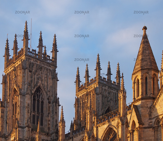 a rear view of the towers at the entrance to york minster in sunlight against a blue cloudy sky