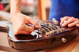 Hand von Gitarrenbauer an E-Gitarre
