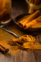 Cinnamon powder in vintage spoon with cinnamon sticks on wooden background as cooking and baking ingredient.