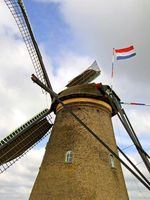 Dutch windmill with flag waving in the wind