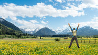Happy succesful Hiker with Backpack jumping with raised arms on Dandelion Flower meadow. Snow covered mountains and traditional house. Bavaria, Alps, Oberstdorf, Rubi, Allgau, Germany.
