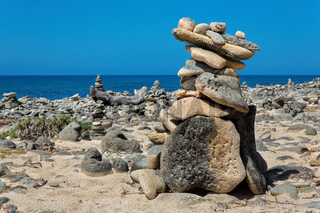 Stack of pebbles on beach of Bonaire with blue sea