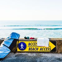 Beach access sign and surfboard