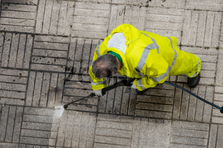 Worker cleaning a sidewalk with pressurized water