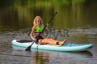 Sitting young woman paddling with SUP on water