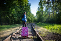 An adult teenager walks with a pink travel suitcase on the railroad tracks straight ahead.