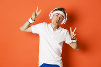 Portrait of carefree middle-aged male athlete, listening music in headphones during fitness training, showing peace signs, standing over orange background