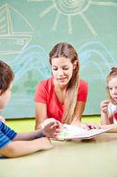 Kindergärtnerin und Kinder lesen Buch im Kindergarten