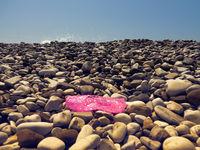 Plastic slipper crumpled and thrown on pebble beach of sea.