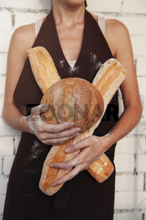 Woman holding fresh bread loaves