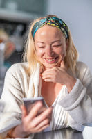 Beautiful caucasian woman at home, feeling comfortable wearing white bathrobe, taking some time to herself, drinking morning coffee and reading news on mobile phone device in the morning