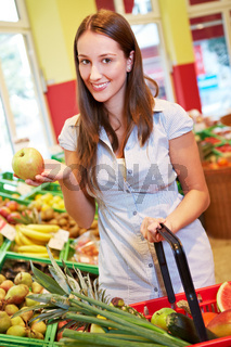 Frau hält Apfel im Supermarkt