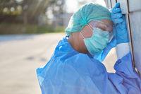 Mediziner in Schutzkleidung ist erschöpft in Pause während Coronavirus Pandemie