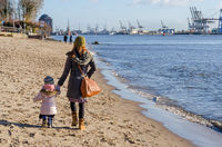 Mother and daughter strolling along the beach at the Elbe river in Hamburg