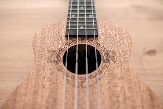 Brown ukulele on wooden background with shallow depht of field
