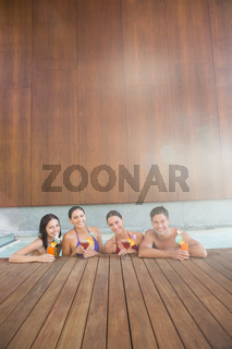 Cheerful people with drinks in the swimming pool