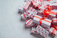 A pile various size wrapped in festive paper boxed gifts placed on stack. Christmas concept