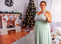 Elegante, übergewichtige Frau mit einem Glas Sekt.