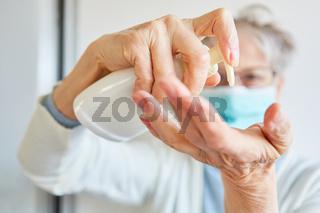 Arzt in Schutzkleidung bei Desinfektion der Hände