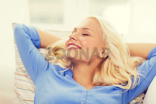 smiling young woman lying on sofa at home