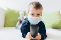 Unhappy young child wearing respiratory mask as prevention against the Coronavirus Covid-19