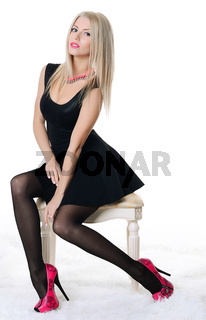 Beautiful sensual woman sits on chair