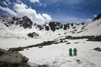 Pair of green snowshoes in snow. High snowy mountains and blue sky